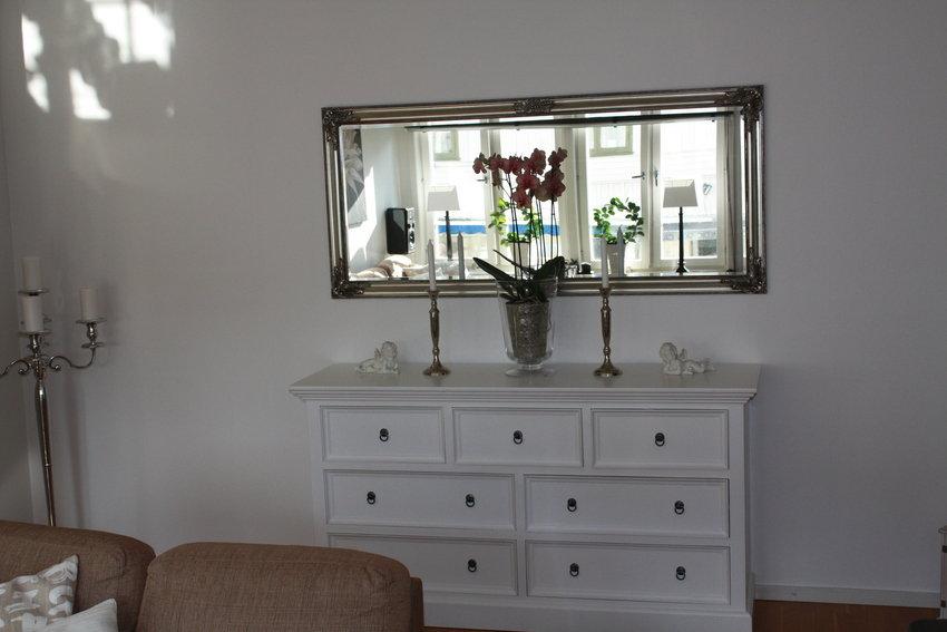 Betongvägg med spegel och byrå